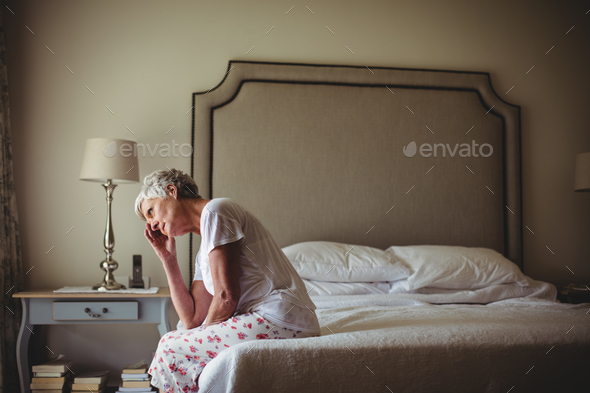 Worried senior woman sitting in bed room - Stock Photo - Images