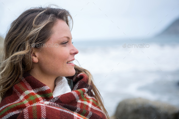 Happy woman wrapped in shawl looking around - Stock Photo - Images