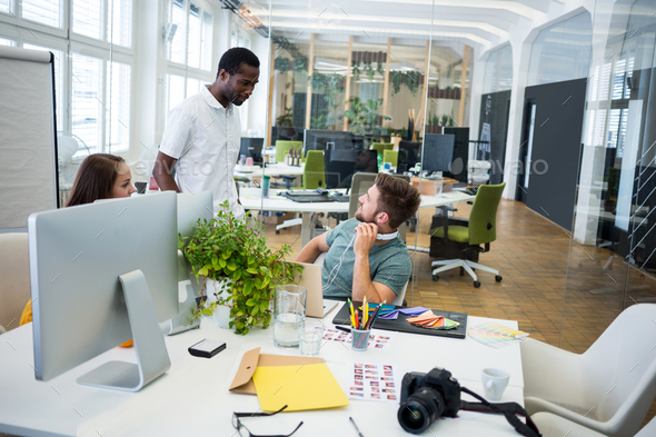 Graphic designers interacting at their desk - Stock Photo - Images