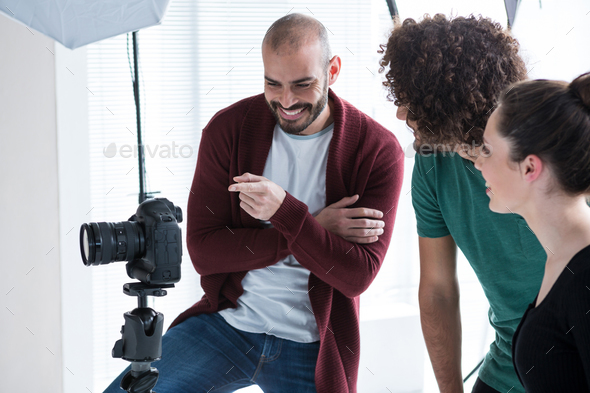 Photographer and his colleagues looking at the photographs in the camera - Stock Photo - Images