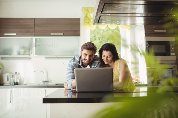 Happy couple using laptop - Stock Photo - Images