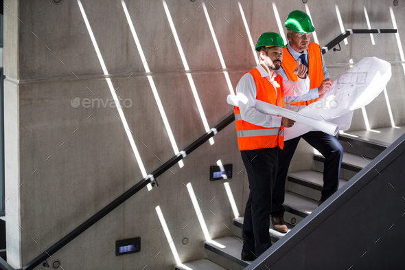 Architects standing on a staircase discussing with blueprint - Stock Photo - Images