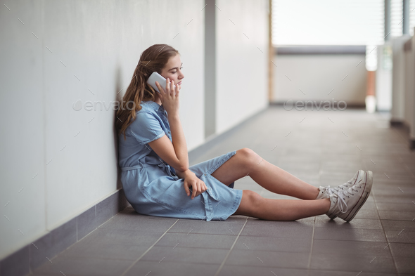 Schoolgirl talking on mobile phone in corridor - Stock Photo - Images