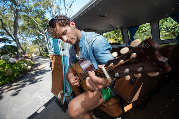 Man playing guitar in campervan - Stock Photo - Images