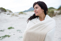 Thoughtful woman wrapped in shawl on beach - PhotoDune Item for Sale