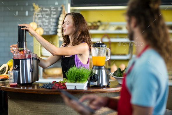 Shop assistant preparing juice at health grocery shop - Stock Photo - Images