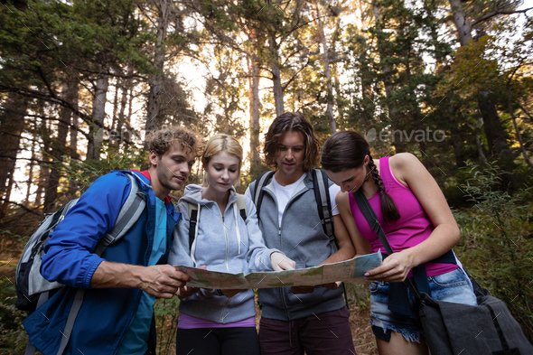 Group of friends looking at the map while hiking - Stock Photo - Images