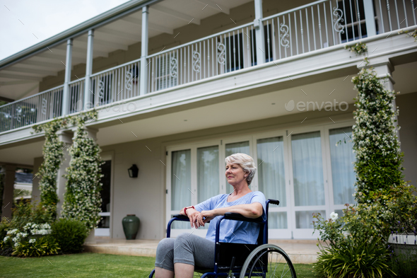 Thoughtful senior woman sitting on wheelchair - Stock Photo - Images