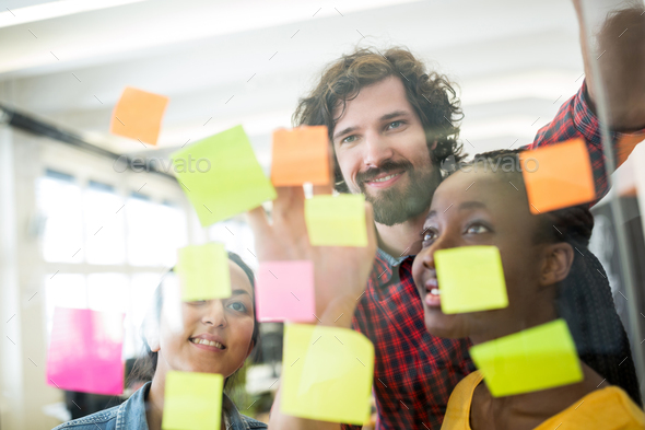 Business executives reading sticky notes - Stock Photo - Images