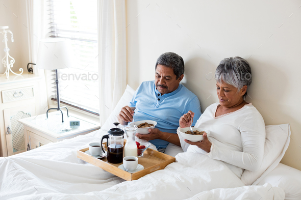 Senior couple having breakfast in bedroom - Stock Photo - Images