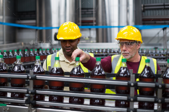 Factory workers monitoring drinks production line - Stock Photo - Images