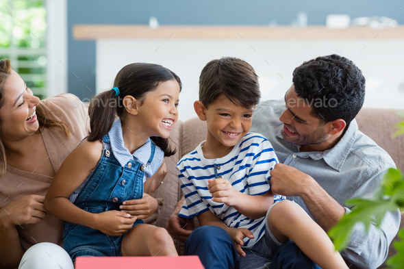 Parents and kids having fun in living room - Stock Photo - Images