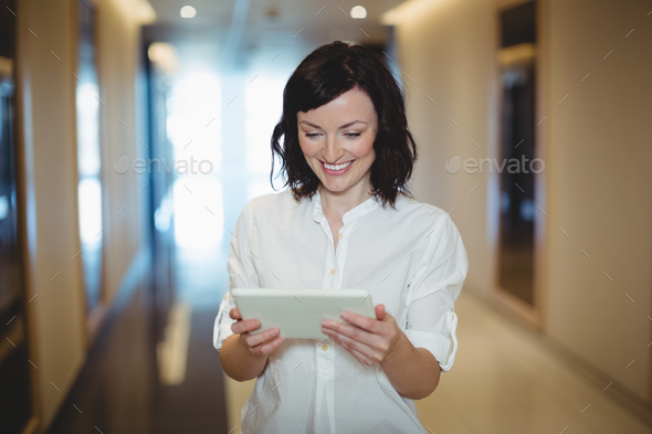 Female business executive using digital tablet in corridor - Stock Photo - Images