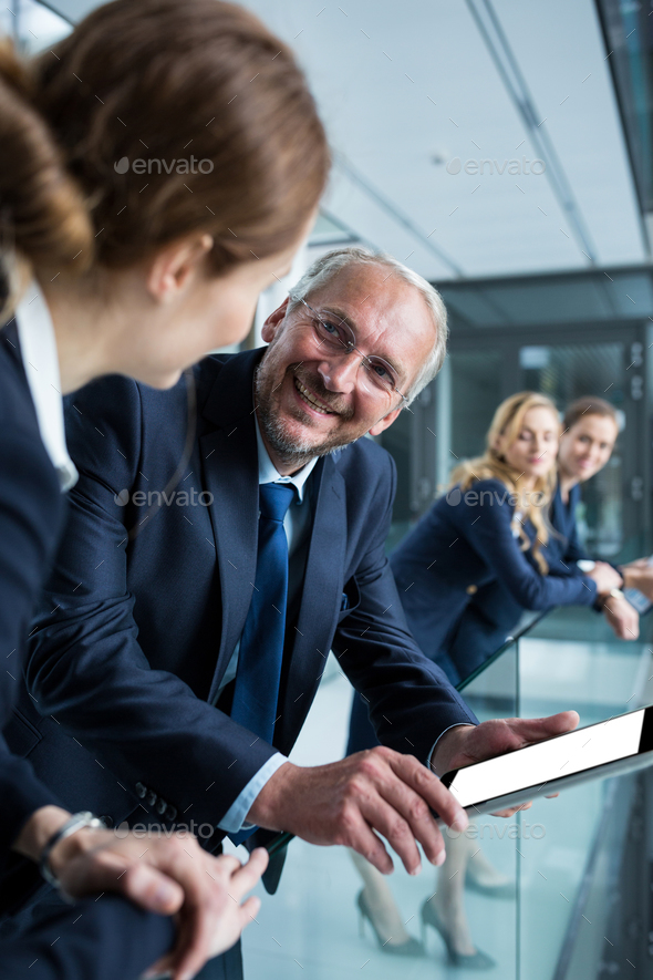 Businessman talking with colleague while holding digital tablet - Stock Photo - Images