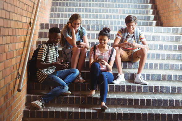 Classmates sitting on staircase and using mobile phone - Stock Photo - Images