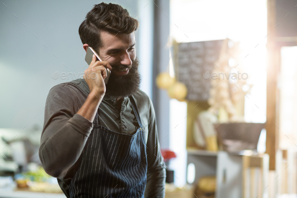 Salesman talking on mobile phone at counter - Stock Photo - Images