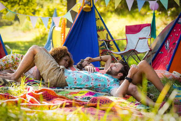 Friends relaxing at campsite - Stock Photo - Images