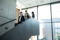 Confident businesswoman with colleagues climbing down the stairs - PhotoDune Item for Sale