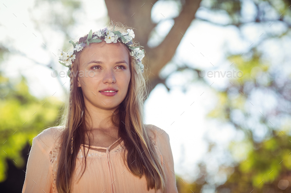 Beautiful woman with flower wreath standing in park - Stock Photo - Images