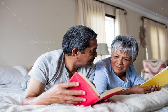 Senior couple reading books on bed - Stock Photo - Images