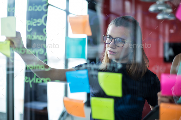 Business executive sticking sticky notes on glass - Stock Photo - Images