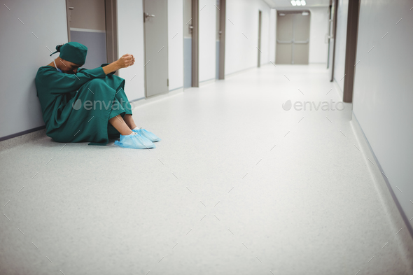 Tensed female surgeon sitting in corridor - Stock Photo - Images