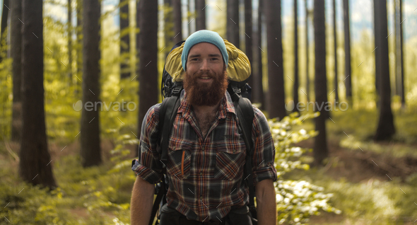 portrait of a caucasian male hiker standing  outdoors in a forest with a backpack - Stock Photo - Images