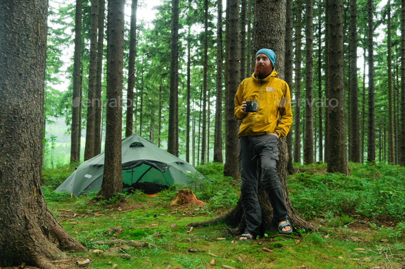 portrait of a caucasian male hiker standing in a forest holding a mug with coffee - Stock Photo - Images