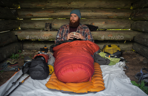 portrait of a caucasian male hiker laying on the ground in his sleeping bag - Stock Photo - Images