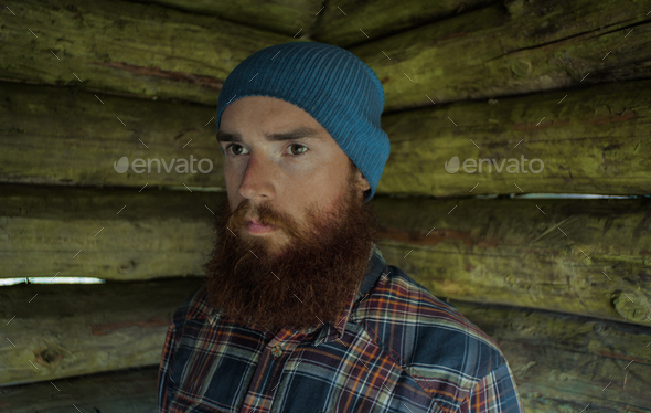 portarit of a ginger caucasian man with beard, wearing a hat and plaid shirt - Stock Photo - Images