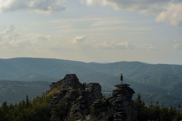 figure standing on a peak of the rock, overlookin landscape, czech republic - Stock Photo - Images