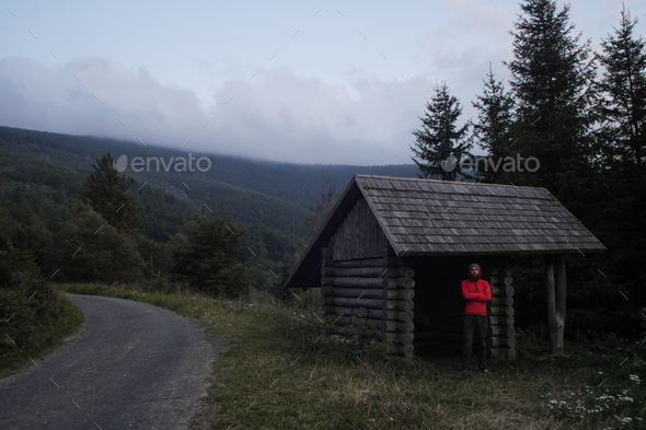 simple wooden cabin used as a hiking shelter with hiker standing inside, czech republic - Stock Photo - Images