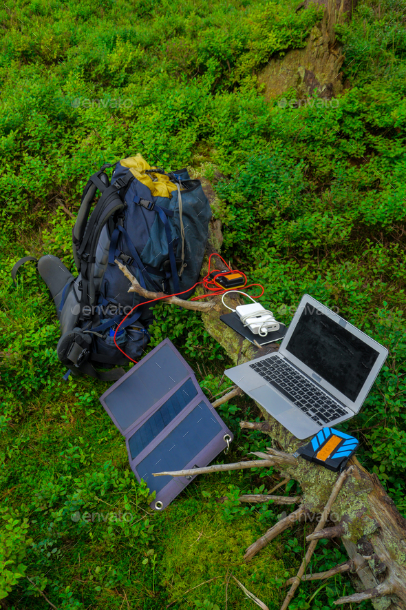 portable technology, solar panel, tablet, laptop and backpack in a forest - Stock Photo - Images
