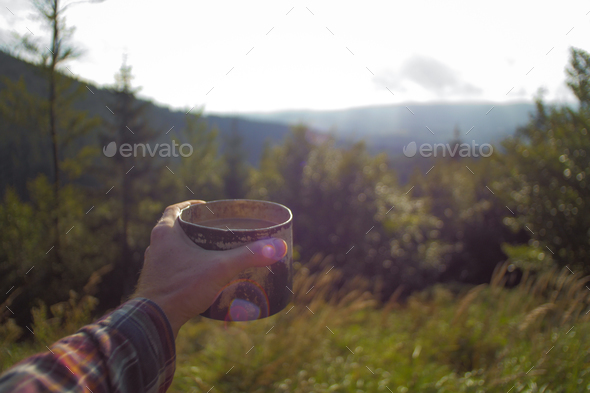 point of a view, mans hand holding a cup of coffee outdoors on a hiking trip - Stock Photo - Images