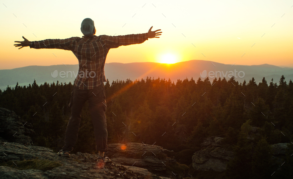 man watching a sunset in a mountain landscape - Stock Photo - Images