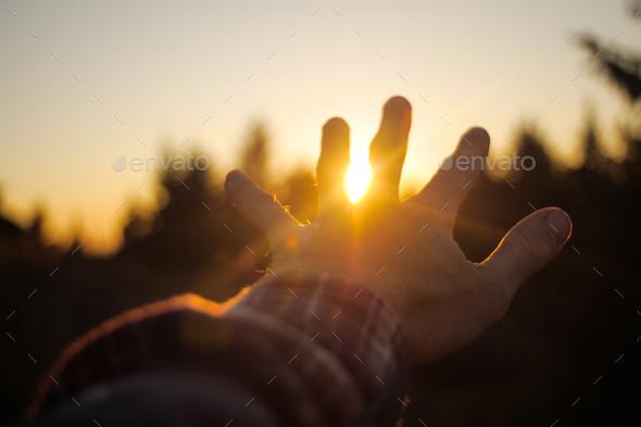 hand waving goodbye to the sunshine/sunset - Stock Photo - Images