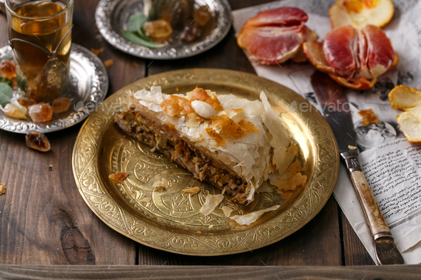Phyllo pastry chicken pie on copper plate with tea, close view - Stock Photo - Images
