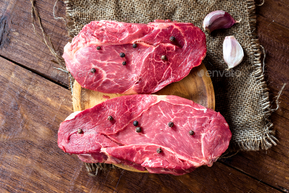 uncooked horse meat steaks on rustic wooden board - Stock Photo - Images
