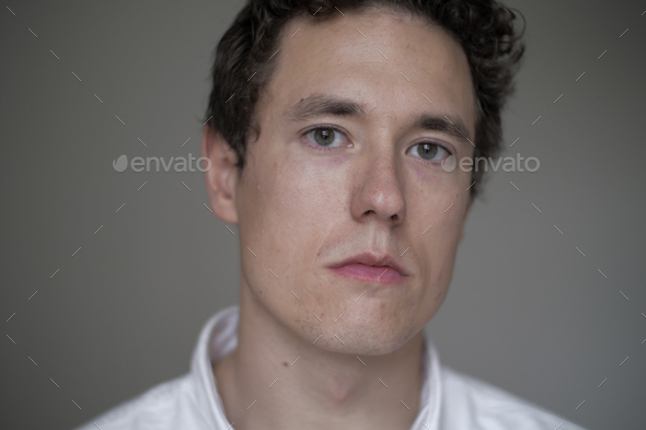 clean portrait of a serious caucasian man wearing a white shirt on a grey background - Stock Photo - Images