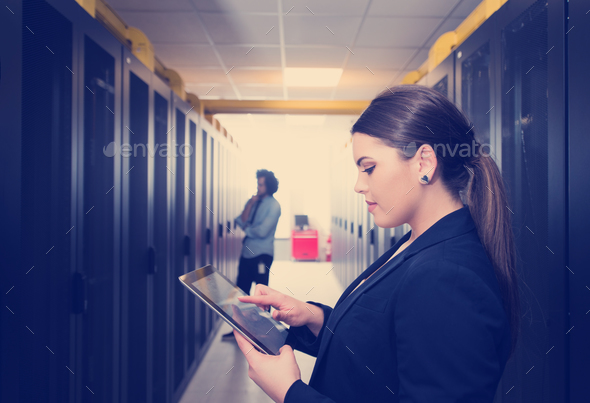 Female engineer working on a tablet computer in server room - Stock Photo - Images