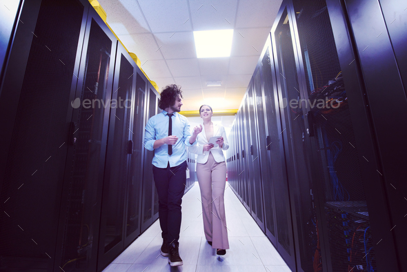 engineer showing working data center server room to female chief - Stock Photo - Images