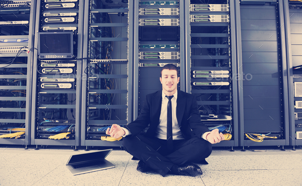 businessman with laptop in network server room - Stock Photo - Images