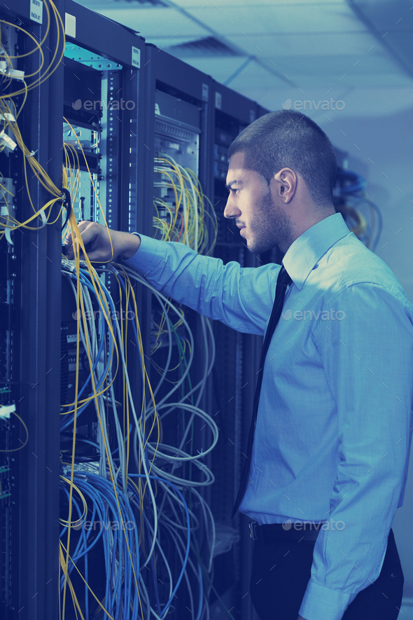 young it engineer in datacenter server room - Stock Photo - Images