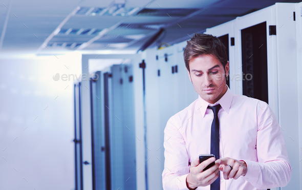 it engeneer talking by phone at network room - Stock Photo - Images
