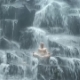 Man Sitting in Yoga Pose at Background Waterfall - VideoHive Item for Sale