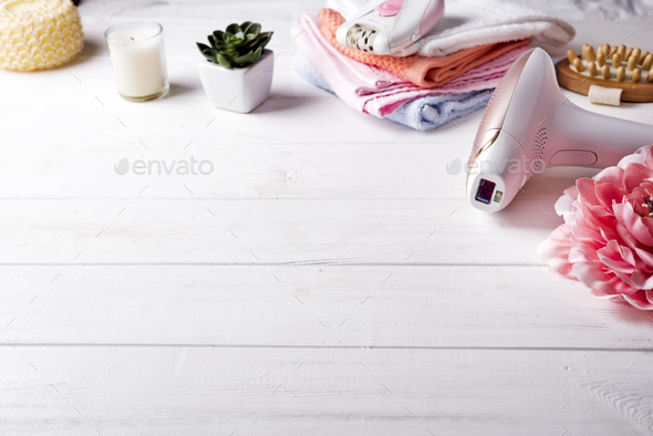 Modern laser epilator with bath accessories on white background. - Stock Photo - Images