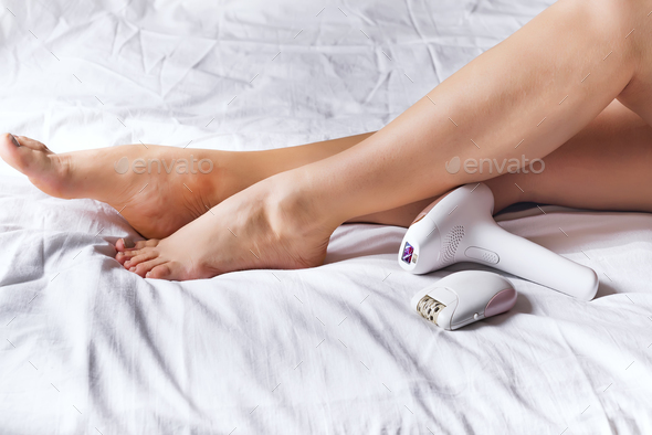 Woman using laser epilator or epilator for hair removal procedure at home - Stock Photo - Images