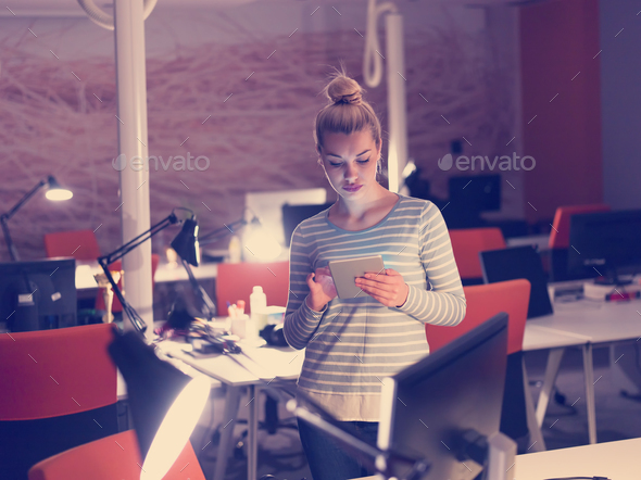 woman working on digital tablet in night office - Stock Photo - Images