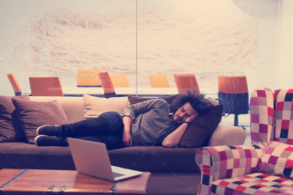 man sleeping on a sofa  in a creative office - Stock Photo - Images