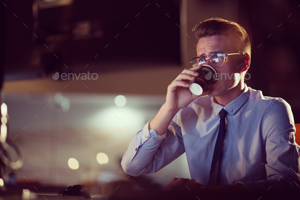 Tired businessman working late - Stock Photo - Images
